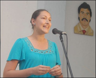 Ailin Labañino, hija de Ramón, habla frente a un micrófono, al fondo un cuandro con imagen de su padre
