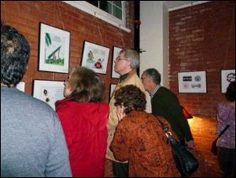 Varias personas contemplan exposición de caricaturas de los Cinco Héroes