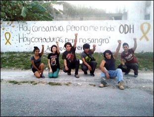 Jóvenes solidarios de Cancún frente a un mural con frase de Antonio Guerrero, uno de los Cinco Héroes Cubanos, pintado por ellos