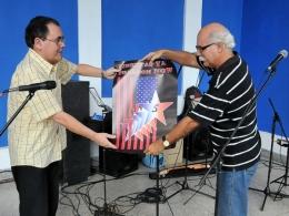 Santiago R. Feliú entregó al doctor Alfredo Espinosa Brito un cancionero sobre Los Cinco y afiches acerca de la temática